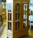Antike Vitrine mit Holzbögen im Glas